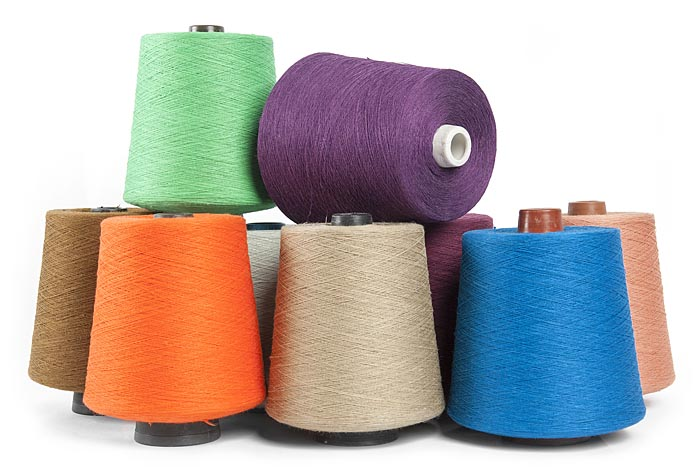 Flax yarn on cones: grey, brown, blue, red, violet, dyed flax yarn, produced in Europe.
